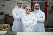 Équipe de bouchers debout avec les bras croisés à l'usine de viande — Photo de stock
