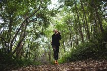 Beautiful woman jogging in forest — Stock Photo