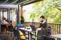 Uomo che utilizza il computer portatile in terrazza bar — Foto stock