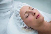 Patient allongé sur le lit tout en recevant un traitement cosmétique en clinique — Photo de stock