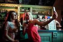 Friends taking selfie from mobile phone while having wine at counter in bar — Stock Photo