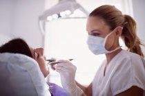 Стоматолог вивчення пацієнтки в клініці — стокове фото