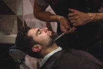 Cliente ottenere barba tagliato con le forbici in negozio di barbiere — Foto stock
