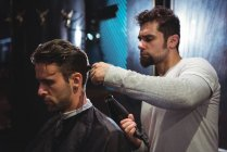 Barber blow drying client hair in barber shop — Stock Photo