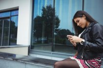 Mulher usando telefone celular fora do prédio de escritórios — Fotografia de Stock