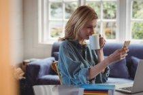 Mulher bonita usando celular enquanto tomando café na sala de estar em casa — Fotografia de Stock