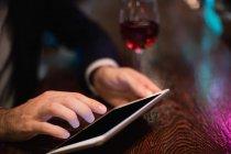 Businessman using digital tablet in bar counter at bar — Stock Photo