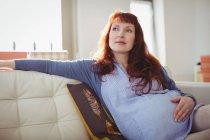 Задумчивая беременная женщина отдыхает в гостиной дома — стоковое фото
