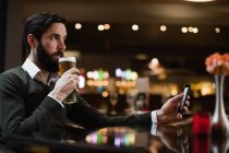 Man holding mobile phone and having glass of beer in bar — Stock Photo