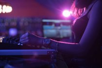 Female dj mixing music on mixing console in bar — Stock Photo
