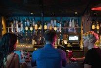 Друзья, пьющие алкогольные напитки за стойкой в баре — стоковое фото
