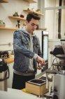 Человек отжимает кофе с фальсификатором в портфильтре в кофейне — стоковое фото