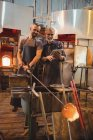 Team of glassblowers using digital while working over a molten glass at glassblowing factory — Stock Photo