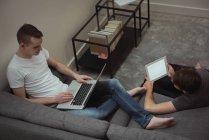 Pareja gay usando tableta digital y portátil en sala de estar en casa - foto de stock