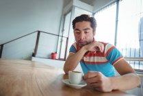 Вдумчивый человек сидит с чашкой кофе на столе в кафе — стоковое фото