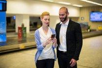 Casal sorridente olhando para o telefone celular na área de espera no terminal do aeroporto — Fotografia de Stock