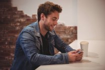 Man using mobile phone at table in cafe — Stock Photo