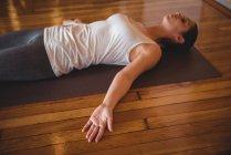Femme adulte moyenne effectuant du yoga dans un studio de fitness — Photo de stock