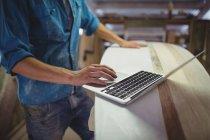 Section médiane de l'homme utilisant un ordinateur portable dans l'atelier de planche de surf — Photo de stock