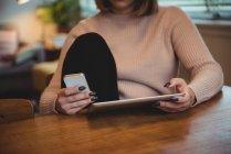 Sezione centrale della donna utilizzando il telefono cellulare e tablet digitale a casa — Foto stock
