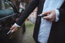 Frau öffnet Autotür mit Fernbedienung an Elektroauto-Ladestation — Stockfoto