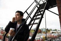 Homme utilisant téléphone portable et boire du café dans le balcon — Photo de stock