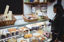Mulher selecionando alimentos embalados no balcão de alimentos no supermercado — Fotografia de Stock