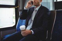 Бізнесмен проведення одноразові корзинч говорити на мобільний телефон під час поїздки в автобусі — стокове фото