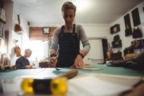 Attentive craftswoman working on a piece of leather in workshop — Stock Photo