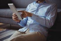 Розділ середині людина, використовуючи цифровий планшетний у вітальні на дому — стокове фото