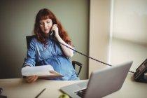 Беременная деловая женщина разговаривает по телефону во время работы в офисе — стоковое фото