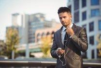 Uomo d'affari che ascolta musica sul cellulare vicino all'edificio degli uffici — Foto stock