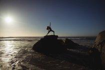 Женщина, занимающаяся йогой на скале в сумерках — стоковое фото
