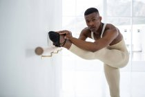 Ballerino alongamento em um barre enquanto praticando dança balé no estúdio — Fotografia de Stock