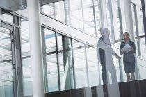 Бизнесвумен взаимодействует с коллегой в коридоре офисного здания — стоковое фото