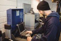Mechaniker mit Laptop in Reparaturwerkstatt — Stockfoto