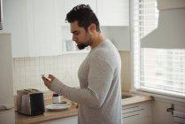 Homme utilisant un téléphone portable dans la cuisine à la maison — Photo de stock