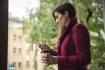 Бізнес-леді проведення чашки одноразові кави і використання мобільного телефону на вулиці — стокове фото