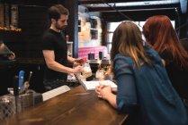 Бармен, подающий пиво клиентам на стойке бара — стоковое фото