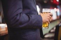 Sezione centrale dell'uomo che tiene il bicchiere di birra nel ristorante — Foto stock