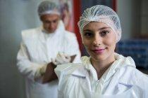 Retrato de açougueiro fêmea sorrindo na fábrica de carne — Fotografia de Stock