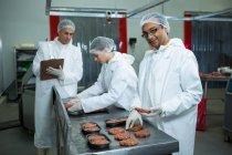 Bouchers emballage galettes sur le comptoir à l'usine de viande — Photo de stock