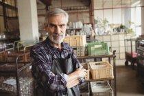 Ritratto di soffiatore in piedi con le braccia incrociate alla fabbrica di soffiaggio del vetro — Foto stock