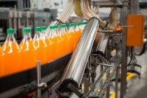 Процесс упаковки бутылок апельсиновых напитков на заводе — стоковое фото