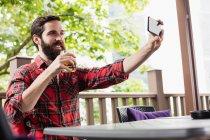 Людини бере на selfie маючи напоєм у барі — стокове фото