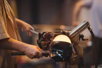 Close-up of glassblower forming and shaping a molten glass at glassblowing factory — Stock Photo
