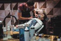 Отражение человека, сбривающего бороду парикмахером с бритвой в парикмахерской — стоковое фото