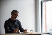 Людина за допомогою мобільного телефону в будинку маючи склянку води — стокове фото