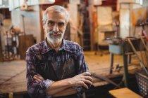 Портрет стеклодува, стоящего со скрещенными руками на стеклодувном заводе — стоковое фото