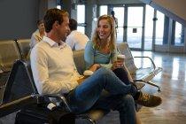 Pareja feliz sentada en la sala de espera en la terminal del aeropuerto - foto de stock